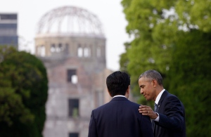 U.S. President Barack Obama, right, and Japanese Prime Minister Shinzo Abe speak with the Atomic Bomb Dome seen at rear at the Hiroshima Peace Memorial Park in Hiroshima, western Japan, Friday, May 27, 2016. (AP Photo/Carolyn Kaster)