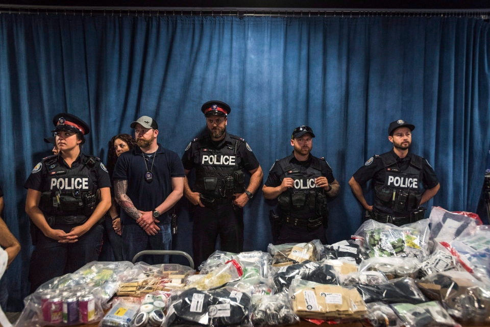 Police officers look on as marijuana products, including edibles and oils, which were confiscated by toronto Police are displayed during a press conference to discuss results of a series of police raids conducted on companies allegedly selling marijuana illegally, dubbed Project Claudia, in Toronto on Friday, May 27, 2016. (The Canadian Press/Aaron Vincent Elkaim)
