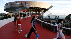 Models walk down a ramp of the Contemporary Art Museum wearing creations from the Louis Vuitton Crusie 2017 collection, in Niteroi, Brazil, Saturday, May 28, 2016. The elite of the fashion world flocked to Brazil, defying an outbreak of the Zika virus, an economic meltdown and the profound political crisis afflicting the country to attend a runway show Saturday by revered French label. The iconic Sugarloaf Mountain is pictured in the background on right. (AP Photo/Leo Correa)