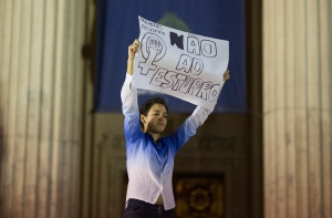 "A woman holds up a sign that reads in Portuguese ""Not to rape"" during a protest against the gang rape of a 16-year-old girl in Rio de Janeiro, Brazil, Friday, May 27, 2016. (AP Photo/Leo Correa)"