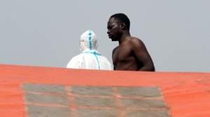 In this photo taken Sunday, May 29, 2016 a migrant attends to disembark from the Italian Navy Vega vessel, in Reggio Calabria, southern Italy, after being rescued in the Mediterranean Sea off the coasts of Libya. Survivor accounts have pushed to more than 700 the number of migrants feared dead in Mediterranean Sea shipwrecks over three days in the past week, even as rescue ships saved thousands of others in daring operations. (AP Photo/Adriana Sapone)