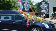 "The hearse carrying the body of Muhammad Ali passes by a mural depicting ""The Greatest of All Time"" on East Broadway Friday, June 10, 2016 in Louisville, Ky. (Jacob Zimmer,/The Courier-Journal via AP)"