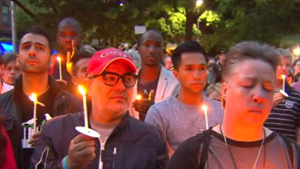 People hold candles at a Toronto vigil for the victims of a gay nightclub shooting in Orlando that left 50 people dead Sunday June 12, 2016.