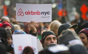In this Jan. 20, 2015, file photo, supporters of Airbnb hold a rally outside city hall in New York. (AP Photo/Bebeto Matthews)