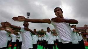 Monsoon clouds loom over as people perform yoga during an event to celebrate International Yoga Day in Gauhati, India, Tuesday, June 21, 2016. (AP Photo/ Anupam Nath)