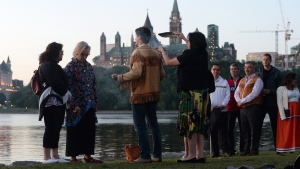 Prime Minister Justin Trudeau takes part in the National Aboriginal Day Sunrise Ceremony on the banks of the Ottawa River in Gatineau, Que., on Tuesday, June 21, 2016. The Canadian Parliament building in Ottawa are seen in the background. THE CANADIAN PRESS/Sean Kilpatrick