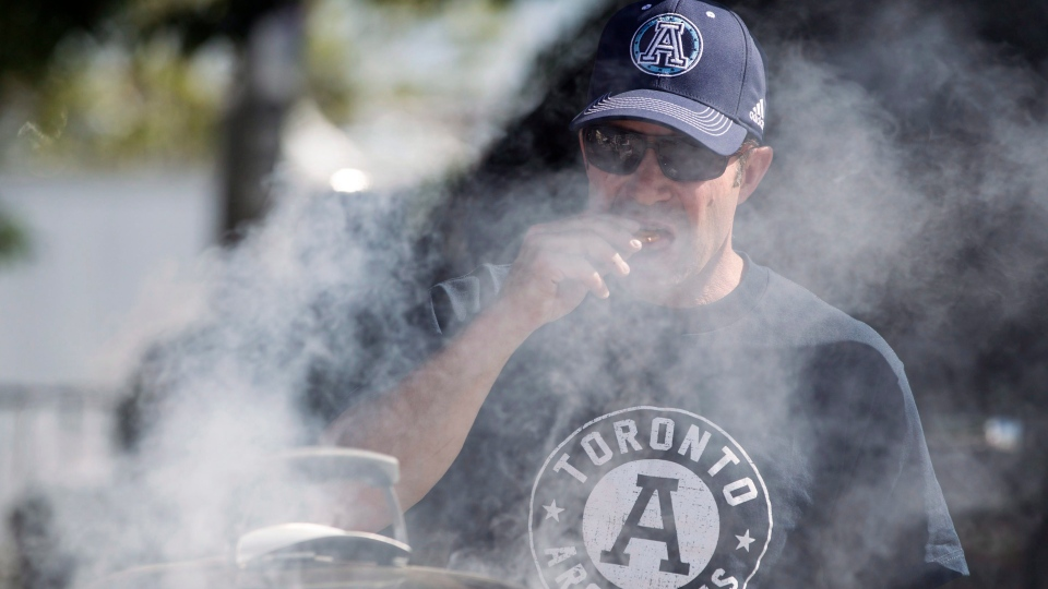 A Toronto Argonauts fan cooks on a grill during a tail gate party ahead of the team's CFL season opener against the Hamilton Tiger-Cats in Toronto on Thursday, June 23, 2016. (The Canadian Press/ Chris Young)