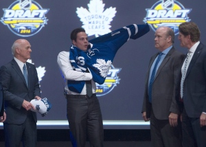 Toronto Maple Leafs first overall pick Auston Matthews pulls on his sweater as he stands on stage with members of the Maple Leafs management team at the NHL draft in Buffalo, N.Y. on Friday, June 24, 2016. (The Canadian Press/Nathan Denette)