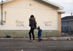 A Women and a young boy walk through the streets in the northern Ontario First Nations reserve in Attawapiskat, Ont., on Monday, April 16, 2016. THE CANADIAN PRESS/Nathan Denette