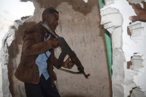 A Somali soldier takes position during an attack on a hotel in Mogadishu, Somalia, Saturday, June 25, 2016 . A Somali police officer says a suicide car bomber detonated an explosives-laden vehicle at the gate of a hotel in Mogadishu followed by gunmen who were fighting their way into the hotel. (AP Photo/Farah Abdi Warsameh)