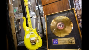 A custom-made signature yellow guitar used by musician Prince sits on display before its auction next to a gold record award for the late musician in Beverly Hills, California, USA, 22 June 2016. The pieces are part of the Entertainment and Music Memorabilia Auction to be held 25 June 2016 at Heritage Auctions. The auction includes 898 other actor's and musician's personally owned items.  EPA/EUGENE GARCIA
