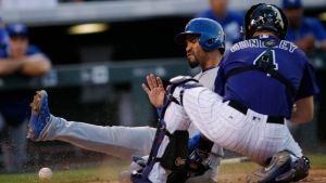 Toronto Blue Jays' Devon Travis, back, slides safely into home plate to score on a double by Josh Donaldson as Colorado Rockies catcher Nick Hundley mishandles the throw in the sixth inning of a baseball game Monday, June 27, 2016, in Denver. Colorado won 9-5. (AP Photo/David Zalubowski)