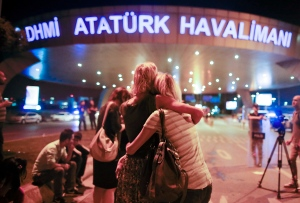 Passengers embrace each other at the entrance to Istanbul's Ataturk airport, early Wednesday, June 29, 2016 following their evacuation after a blast.  (AP Photo/Emrah Gurel)