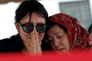 Mourners react next to the coffin during the funeral for Gulsen Bahadir, 28, a Turkish Airlines (THY) flight attendant killed Tuesday at the blasts at Ataturk airport, in Istanbul,Wednesday, June 29, 2016. (AP Photo/Emrah Gurel)