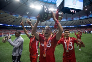 Toronto FC's Eriq Zavaleta, centre, hoists the Voyageurs Cup while celebrating with teammates goalkeeper Quillan Roberts, left, Jay Chapman, back left, and Marky Delgado, right, after defeating the Vancouver Whitecaps on aggregate in the Canadian Championship soccer final in Vancouver, B.C., on Wednesday June 29, 2016. THE CANADIAN PRESS/Darryl Dyck