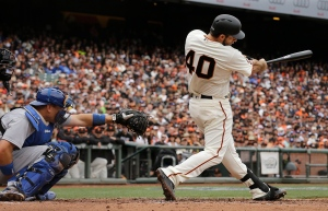 In this April 9, 2016, file photo, San Francisco Giants' Madison Bumgarner (40) hits a solo home run in front of Los Angeles Dodgers catcher A.J. Ellis during the second inning of a baseball game in San Francisco. San Francisco manager Bruce Bochy said he plans to use his slugging pitcher Bumgarner instead of a designated hitter Thursday, June 30, 2016, night when the Giants visit the Oakland Athletics. (AP Photo/Jeff Chiu, File)