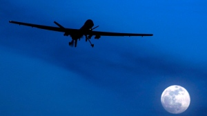 In this Jan. 31, 2010 file photo, an unmanned U.S. Predator drone flies over Kandahar Air Field, southern Afghanistan, on a moon-lit night.  Putting the U.S. military in charge of drone strikes in Iraq and Syria is leading to reduced congressional scrutiny.   Some officials and activists fear that means a greater risk of civilian casualties.   (AP Photo/Kirsty Wigglesworth, File)