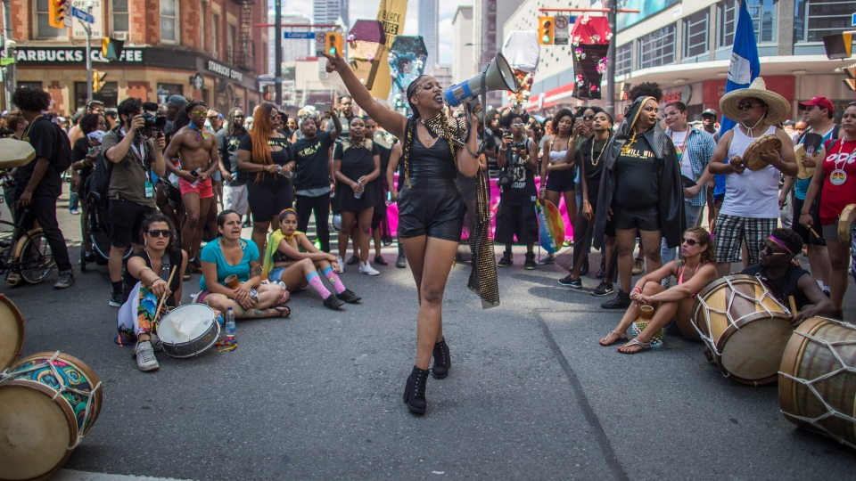 People from the Black Lives Matter sit on the ground to halt the annual Pride Parade, in Toronto on Sunday, July 3, 2016. THE CANADIAN PRESS/Mark Blinch