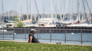 A man enjoys the hot weather at Coronation Park, near Lake Shore Boulevard, in Toronto in June 2016. (THE CANADIAN PRESS/Eduardo Lima)