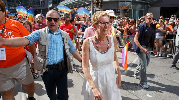 Ontario Premier Kathleen Wynne, centre, finishes her march in the annual Pride Parade along Yonge and Dundas Streets in Toronto on Sunday, July 3, 2016. THE CANADIAN PRESS IMAGES/Michael Hudson