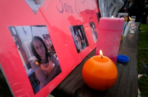 Lit candles and photographs are seen on display at a vigil for Calgary homicide victims Sara Baillie and her five-year-old daughter Taliyah Marsman, in Calgary, on Sunday, July 17, 2016. THE CANADIAN PRESS/Jeff McIntosh