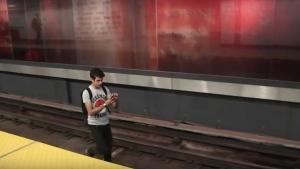 Comedian Mark Correia walks along TTC subway tracks looking for Pokemon in a still image from a YouTube video. (Noodle Boys/ YouTube)