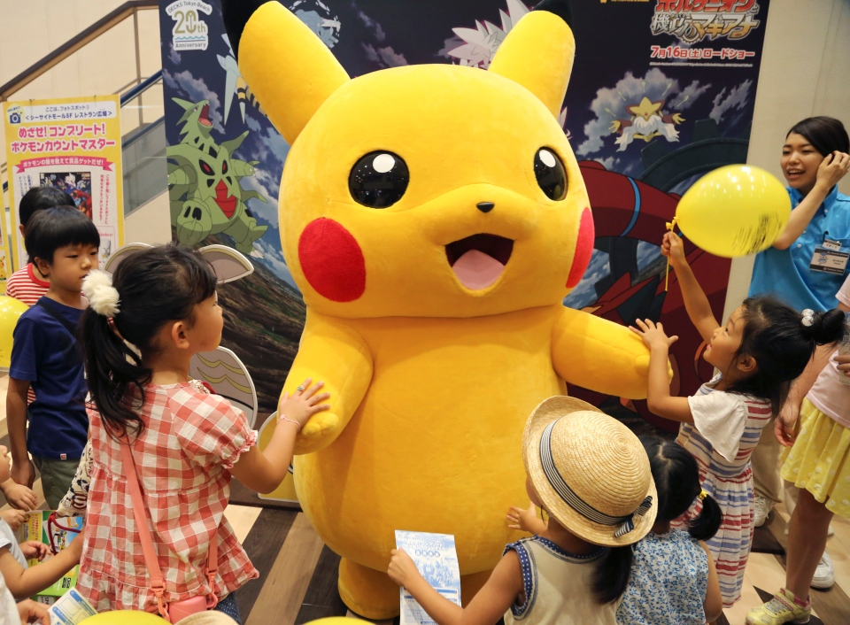 In this Monday, July 18, 2016 photo, a stuffed toy of Pikachu, a Pokemon character, is surrounded by children during a Pokemon festival in Tokyo. (AP Photo/Koji Sasahara)