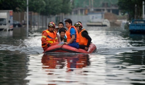 In this Thursday, July 21, 2016, photo, rescuers use a raft to transport people along a flooded street in Shenyang in northeastern China's Liaoning Province. Dozens of people have been killed and dozens more are missing across China after a round of torrential rains swept through the country earlier this week, flooding streams, triggering landslides and destroying houses. (Chinatopix Via AP)