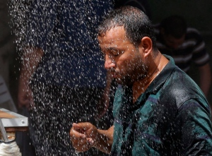 In this Wednesday, July 20, 2016 file photo, an Iraqi man cools off the summer heat by using an open air shower in Baghdad, Iraq. Iraqis are enduring the year's hottest day to date, with temperatures soaring to 51 Celsius degrees (123.8 Fahrenheit) in Baghdad and as much as 53 Celsius (127.4 Fahrenheit) in the southern part of the country. (AP Photo/Karim Kadim, File)