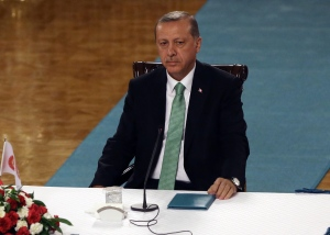 Turkey's President Recep Tayyip Erdogan waits to address a group of lawmakers from the ruling party at the parliament in Ankara, Turkey, Friday, July 22, 2016. Parliament voted 346-115 to approve the national state of emergency, which gives sweeping new powers to President Recep Tayyip Erdogan, who had been accused of autocratic conduct even before this week's crackdown on alleged opponents. Erdogan has said the state of emergency will counter threats to Turkish democracy. (AP Photo/Burhan Ozbilici)
