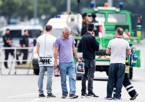 The father of a victim, center, holds a picture of his son near the Olympia shopping center where a shooting took place leaving nine people dead the day before on Saturday, July 23, 2016 in Munich, Germany. (AP Photo/Sebatian Widmann)