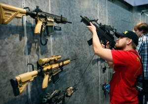 In this Jan. 19, 2016 file photo, Nolan Hammer looks at a gun at the Heckler & Koch booth at the Shooting, Hunting and Outdoor Trade Show in Las Vegas. Nearly two-thirds of Americans expressed support for stricter gun laws, according to an Associated Press-GfK poll released Saturday, July 23, 2016. A majority of poll respondents favor a nationwide ban on the sale of semi-automatic assault weapons such as the AR-15. (AP Photo/John Locher, File)