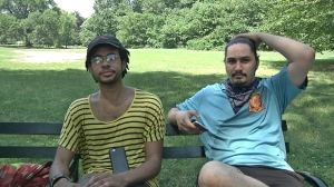 "In this July 13, 2016 frame grab from video, Jordan Clark, left, and Lewis Gutierrez sit in Prospect Park as they talk about their new ""Pokemon Go"" business in the Brooklyn borough of New York. They are among the new entrepreneurs who offer their services as ""trainers"" for the game at $20 per hour - logging onto a client's ""Pokemon Go"" account and effectively running up their score while a client is stuck at work or sitting in class. (AP Photo/Ezra Kaplan)"