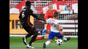 Toronto FC's Sebastian Giovinco shoots the ball on goal as DC United's goalkeeper Travis Worra and Kofi Opare defend during first half MLS soccer action in Toronto on Saturday, July 23, 2016. THE CANADIAN PRESS/Frank Gunn