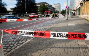 Police have cordoned off an area in inner city Reutlingen, Germany, Sunday, July 24, 2016. A man killed a woman with a machete and injured two other people in the area. The man has been arrested. (CHRISTOPH SCHMIDT/dpa via AP)