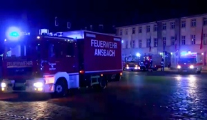 In this image taken from video fire trucks and ambulances stand in the city center of Ansbach near Nuremberg, southern Germany, Monday morning, July 25, 2016, after a man was killed when an explosive device he was believed to be carrying went off near an open-air music festival, injuring 10 others. (News5 via AP)