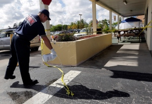 A Fort Myers fire fighter pours bleach over blood stains on the pavement at the scene of a deadly shooting outside the Club Blu nightclub in Fort Myers, Fla., Monday, July 25, 2016. (AP Photo/Lynne Sladky)