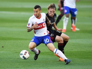 Toronto FC's Sebastian Giovinco, left, moves the ball past DC United's Jared Jeffrey during first half MLS soccer action in Toronto on Saturday, July 23, 2016. (The Canadian Press/Frank Gunn)