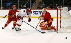 Denver forward Trevor Moore (8) and Ferris State defenseman Ryan Lowney, left, chase a shot after it was deflected by Ferris State goalie Darren Smith, right, during the first period of an NCAA men's hockey West Regional championship in St. Paul, Minn., Sunday, March 27, 2016. (AP Photo/Ann Heisenfelt)