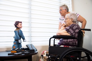 Elizabeth Graner, who has dementia, sits in her wheelchair as her daughter Penny Blake helps her interact with Ludwig, a two-foot-tall robot created by University of Toronto researchers to engage people with Alzheimer's disease and dementia, at a press conference on Tuesday, July 26, 2016. THE CANADIAN PRESS/Michelle Siu