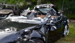 This photo provided by the NTSB via the Florida Highway Patrol shows the Tesla Model S that was being driven by Joshau Brown,who was killed, when the Tesla sedan crashed while in self-driving mode on May 7, 2016. (NTSB via Florida Highway Patrol via AP)
