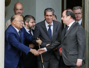 French President Francois Hollande shakes hands with Paris Mosque rector Dalil Boubakeur, left, after a meeting with religious representatives at the Elysee Palace in Paris, following yesterday attack at a church in Normandy, Wednesday, July 27, 2016. The Islamic State group crossed a new threshold Tuesday in its war against the West, as two of its followers targeted a church in Normandy, slitting the throat of an elderly priest celebrating Mass and using hostages as human shields before being shot by police. (AP Photo/Thomas Padilla)