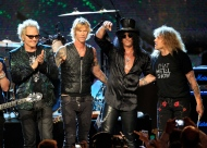 """FILE - In this April 15, 2012 file photo, Guns N' Roses, from left, Matt Sorum, Duff McKagan, Slash and Steven Adler appear on stage at their induction into the Rock and Roll Hall of Fame in Cleveland. Frontman Axl Rose skipped the event, saying it didn't """"appear to be somewhere I'm actually wanted or respected."""" (AP Photo/Tony Dejak, File)"""
