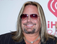 FILE - In this Sept. 19, 2014 file photo, Vince Neil arrives at the iHeart Radio Music Festival in Las Vegas. The 55-year-old Motley Crue frontman was issued a misdemeanor battery summons following a report of a scuffle with a woman at a Las Vegas Strip resort. Police said Friday, April 8, 2016, that Neil is accused of grabbing a woman's hair from behind and pulling her to the ground on Thursday outside the Aria resort.( Photo by Andrew Estey/Invision/AP, File)