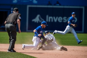 Toronto Blue Jays second baseman Devon Travis, left, misses the tag against as San Diego Padres' Travis Jankowski steals second base during ninth inning MLB interleague baseball action in Toronto on Wednesday, July 27, 2016. THE CANADIAN PRESS/Aaron Vincent Elkaim
