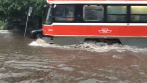 A streetcar cuts through flood water s covering Queen Street in the Beaches after a heavy storm Wednesday July 27, 2016. (Ruthann Clayton /Submitted)