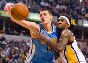 Nuggets center Nikola Jokic (15) reaches to regain control of the ball as Pacers center Jordan Hill (27) applies the defense during the first half of an NBA basketball game, Saturday, Jan. 30, 2016, in Indianapolis. (AP Photo/Doug McSchooler)