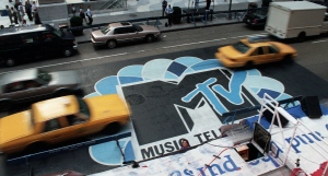 In this Sept. 3, 1996, file photo, traffic moves along 6th Avenue in New York, over the logo painted in the street outside Radio City Music Hall for the MTV Music Video Awards ceremony. MTV announced July 28, 2016, that it is rebranding VH1 Classic as MTV Classic and the channel will focus on 1990s and early 2000s nostalgia. (AP Photo/Todd Plitt, File)