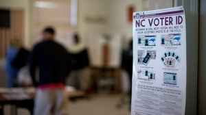 This photo taken March 15, 2016, shows a NC Voter ID rules posted at the door of the voting station at the Alamance Fire Station in Greensboro, N.C. A federal appeals court on Friday, July 29, 2016,  blocked a North Carolina law that required voters to produce photo identification and follow other rules disproportionately affecting minorities, finding that the law was intended to make it harder for blacks to vote in the presidential battleground state. (Andrew Krech/News & Record via AP)