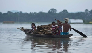 A flood affected family moves on a boat at Sildubi village, in the northeastern Indian state of Assam, Friday, July 29, 2016. Torrential monsoon rains have caused widespread flooding in Assam state and forced around 1.2 million people to leave their water-logged homes. (AP Photo/Anupam Nath)